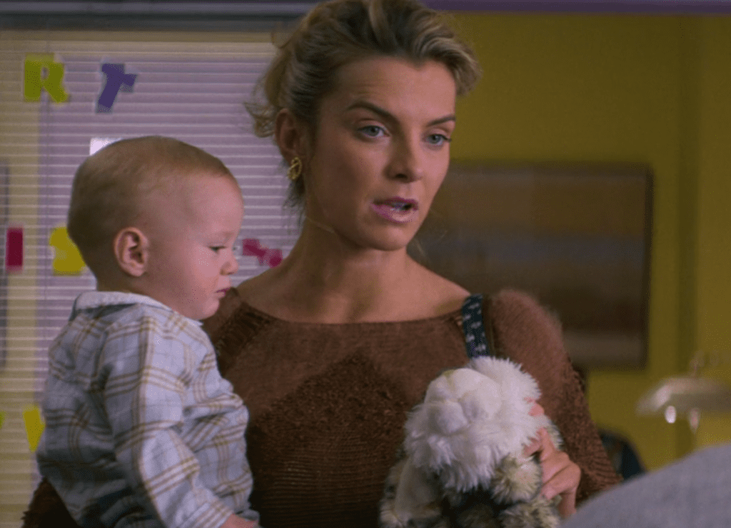Debbie dropping off her baby son at day care, handing the day care worker her son's plush toy.