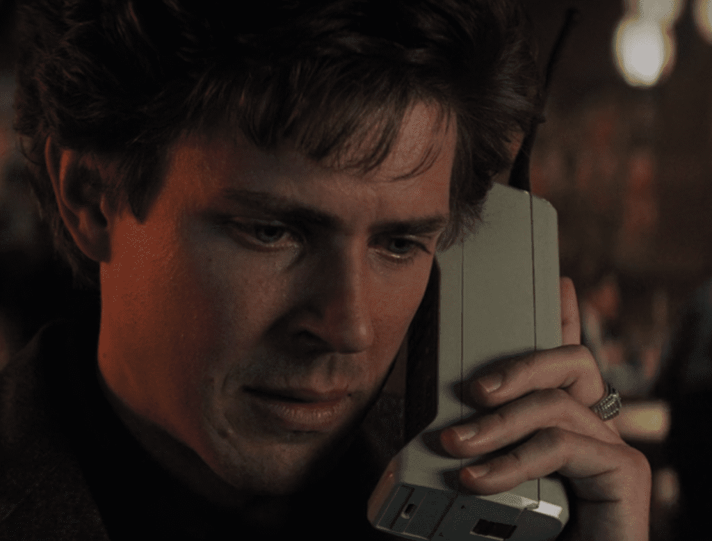 Bash on a very old clunky mobile telephone, face serious as he receives bad news from the hospital.