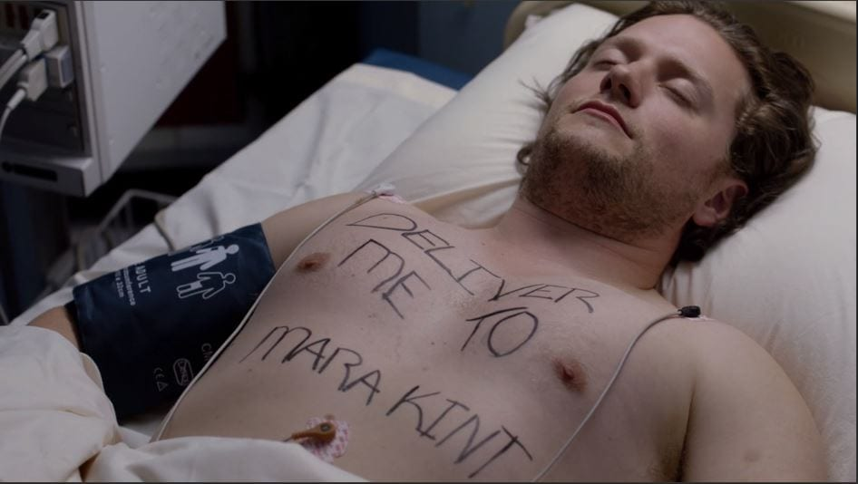 """A man in a bed with """"Deliver me to Mara Kint"""" written across his chest"""
