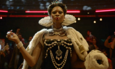 Elektra walks in the ball wearing a crown, white ruffled collar, bejeweled gown, and fur cape, that look like they are from 1600s European royalty.
