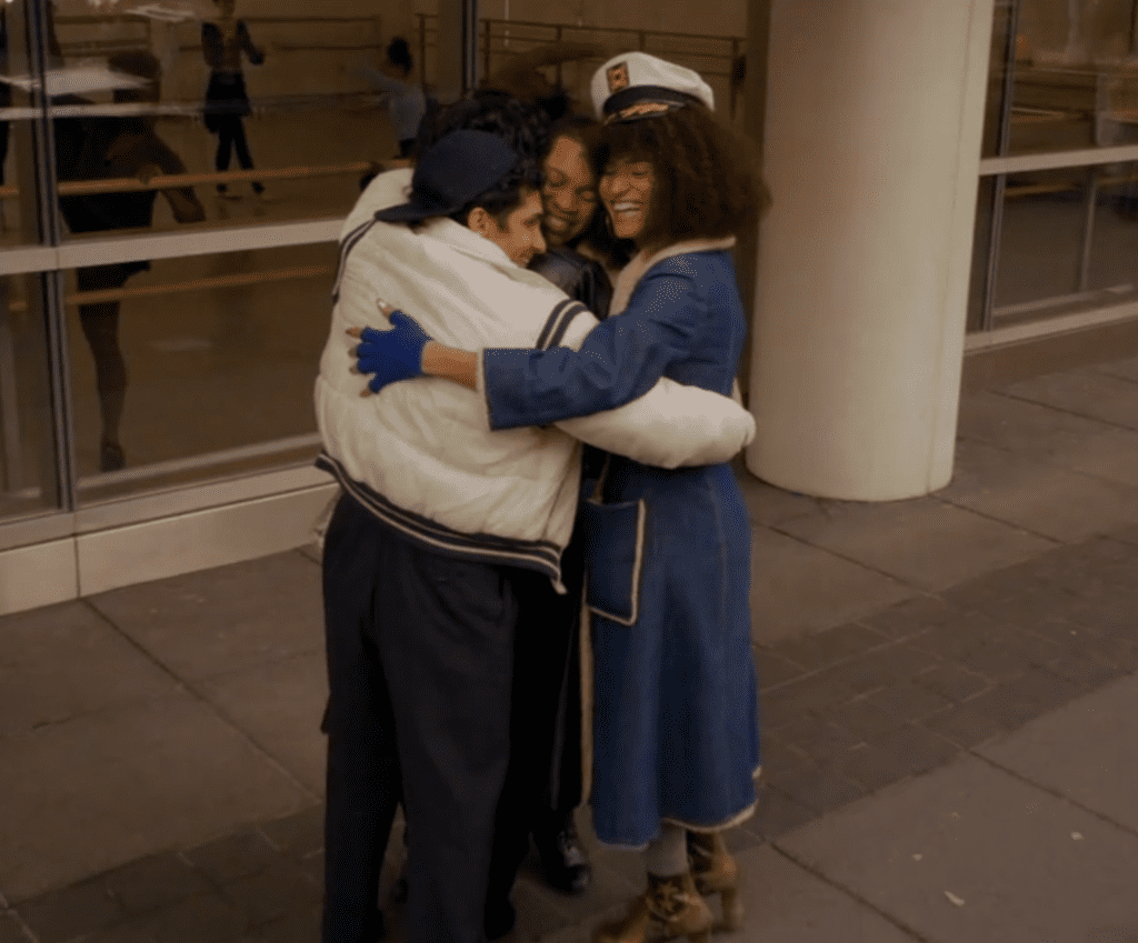 Blanca, Lil Papi, and Angel all envelop Damon in a group hug on the sidewalk outside the school of dance. They are all laughing. Lil Papi wears a puffy white jacket and baseball cap. Angel wears a long blue coat, blue gloves, high heels, and a captain hat.