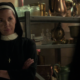 Sister Maggie stands with arms crossed and a skeptical look on her face. She is wearing her full nun habit. Shelves of church paraphenalia are in the background.