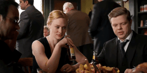Matt, Karen and Foggy sit around a table with food and bottles of beer in front of them.