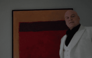 Fisk stands in front of a painting, wearing a crisp white suit. The painting is a black and red rectangle on an orange background.