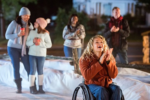 a blonde curly haired woman in a wheelchair wearing a rust orange jacket and jeans against backdrop of snow and people clapping