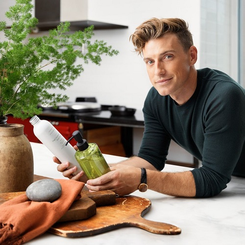 White mean wearing dark green long-sleeve shirt leaning over kitchen island with home products.