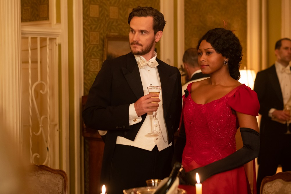 White man in suit and Black woman in red dress