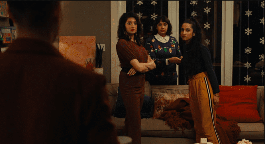 Three Pakistani sisters looking at character whose back is facing to the camera in syed family xmas eve game night